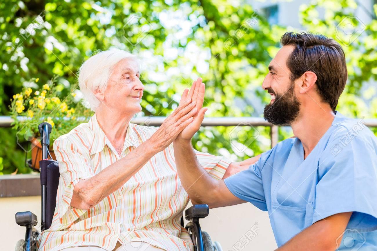 Senior woman and nurse giving High five in nursery home Standard-Bild - 47847033
