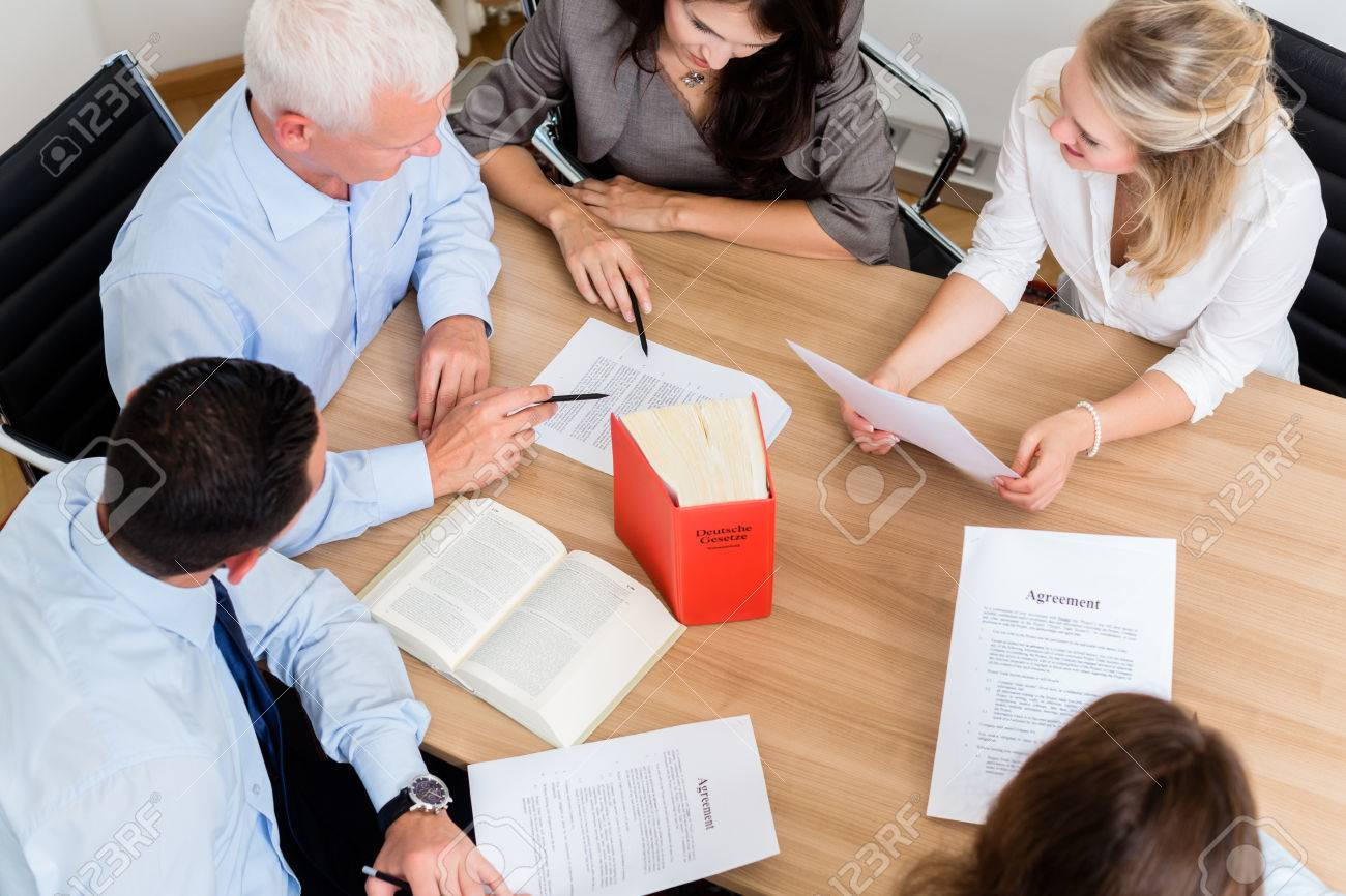 Lawyers in law firm reading documents and agreements at large conference table Standard-Bild - 47847143