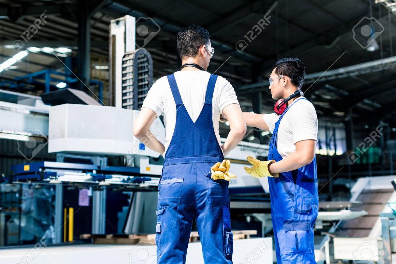 Worker team in factory discussing in front of machine Standard-Bild - 47847215