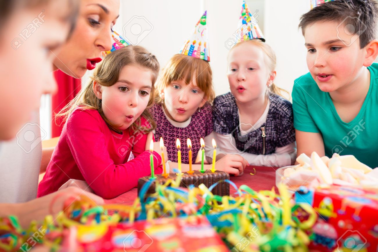Child on birthday party blowing candles on cake being helped by friends and the mother Standard-Bild - 51585948