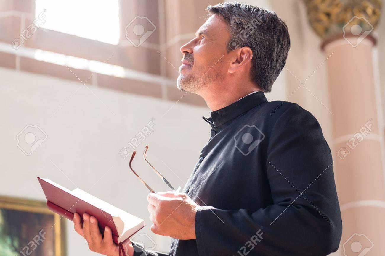 Catholic priest reading bible in church Standard-Bild - 51586041