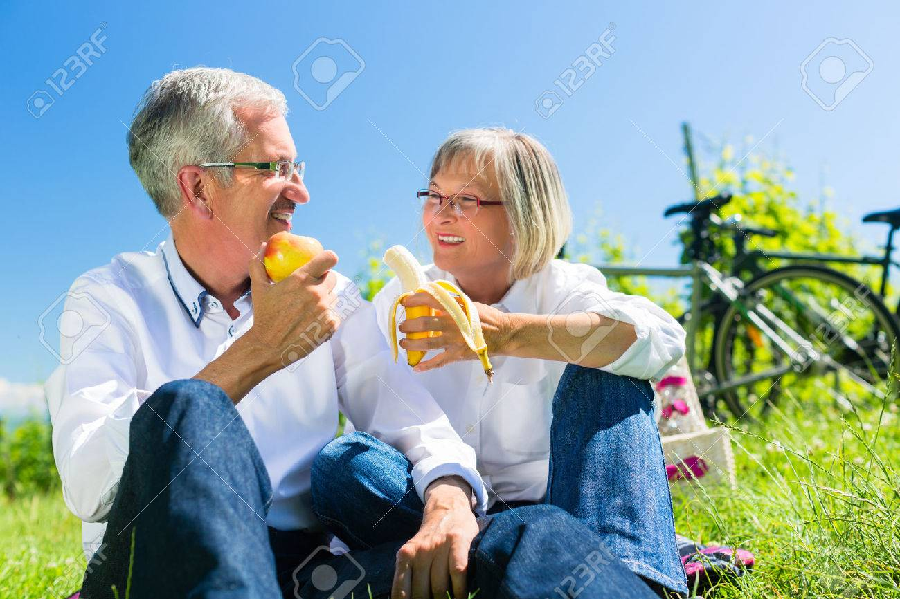 Senior couple eating fruit and drinking at picnic in summer, beautiful landscape in the background Standard-Bild - 51586232