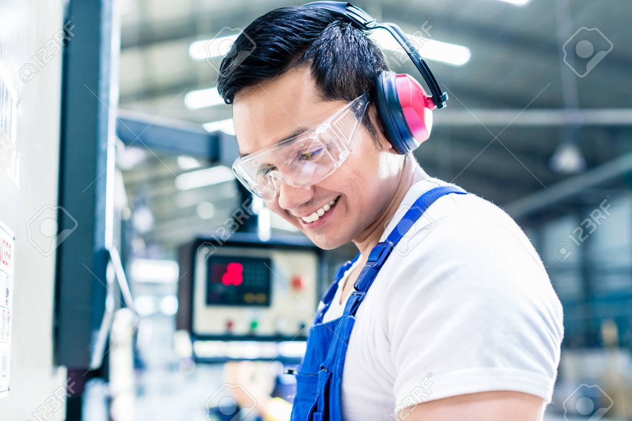 Asian machine operator in production plant checking data Standard-Bild - 51586368