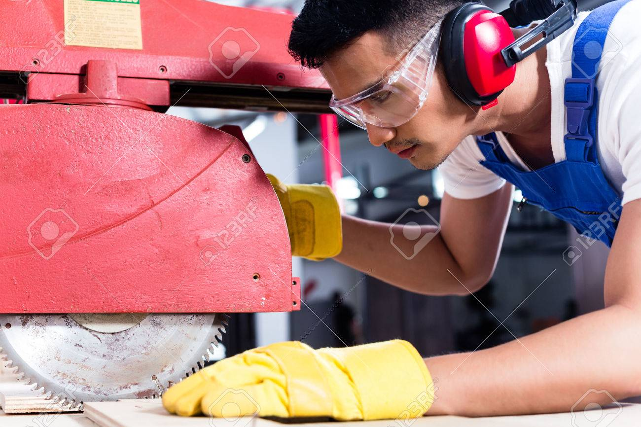 Carpenter in Asian workshop with circular saw in a manufacturing factory Standard-Bild - 51756018