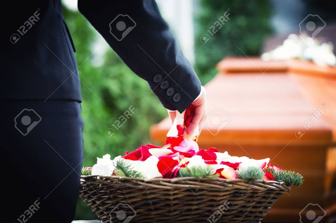 Woman on funeral putting rose petals on coffin Standard-Bild - 51755983