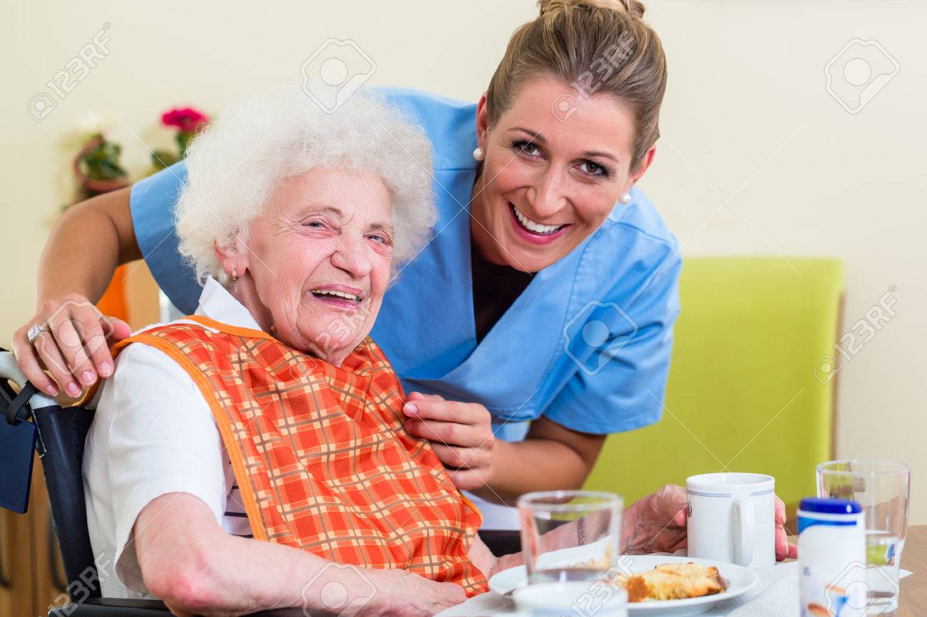 Nurse with senior woman helping with meal Standard-Bild - 51756039