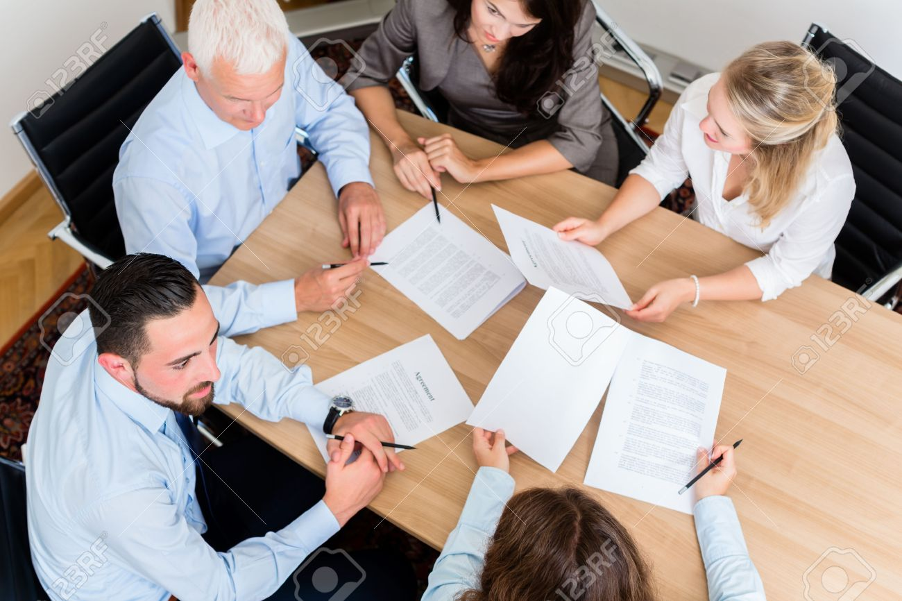 Lawyers having team meeting in law firm reading documents and negotiating agreements Standard-Bild - 51756055