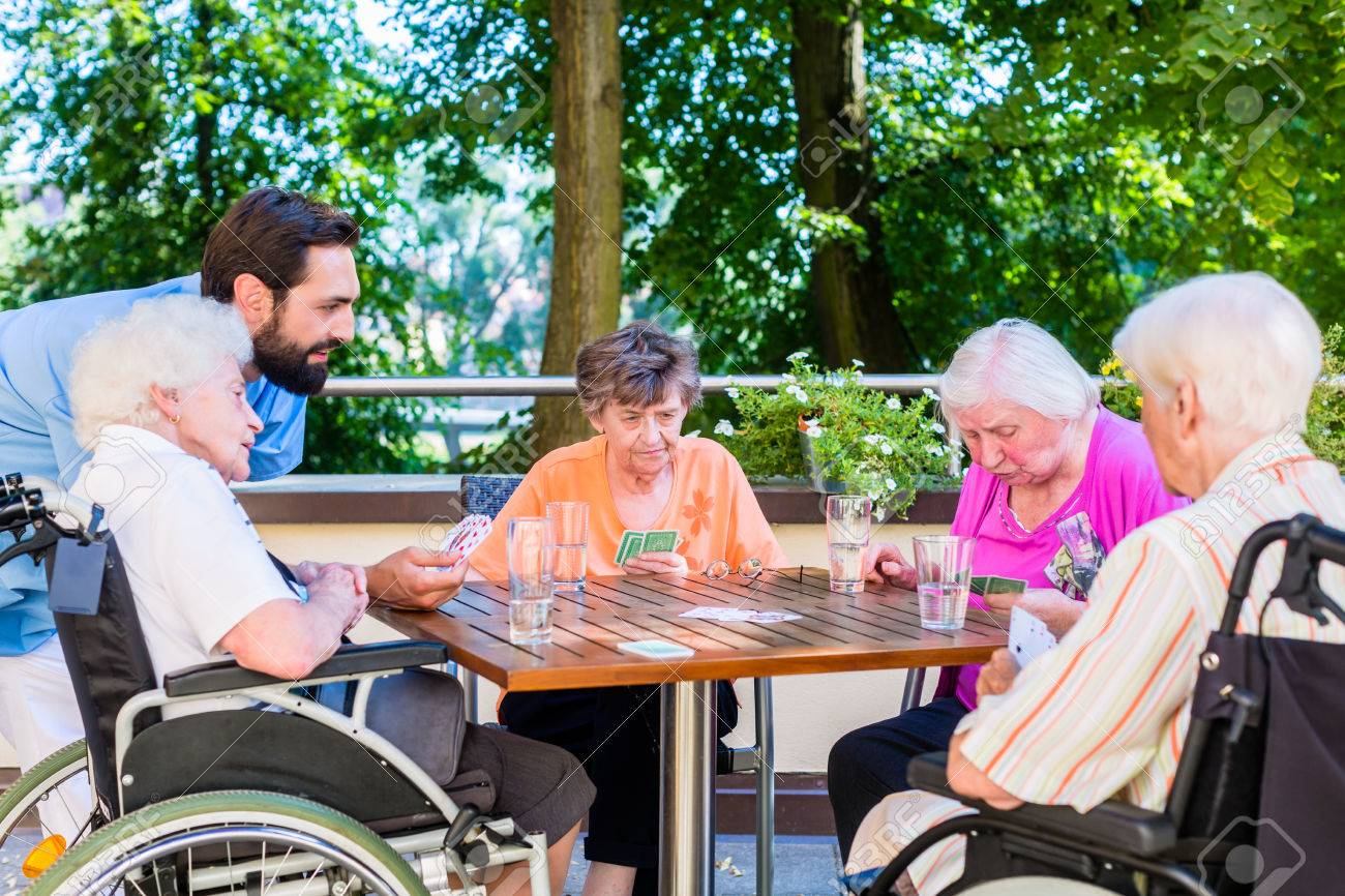Group of seniors and nurse playing cards in rest home Standard-Bild - 51756076
