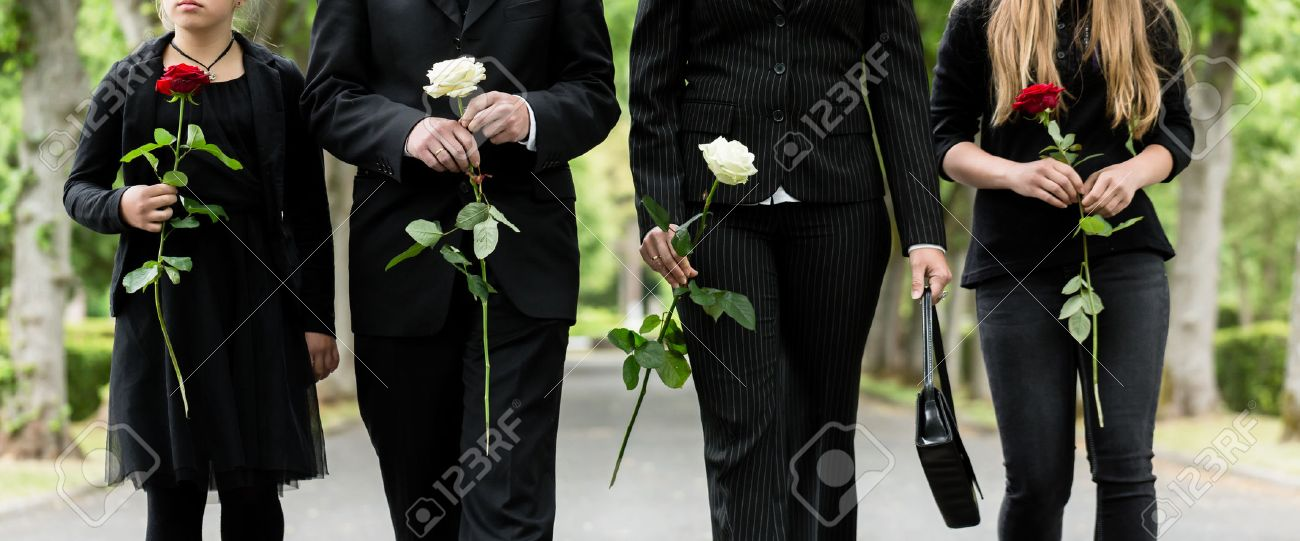 Torso of family on cemetery mourning holding red and white roses in hands Standard-Bild - 55421088