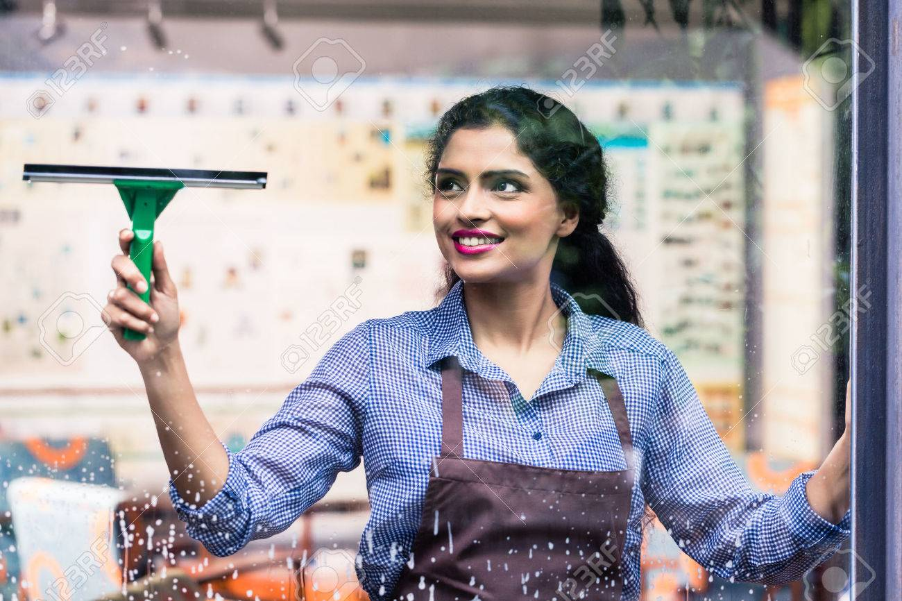 Indian employee cleaning windows with squeegee Standard-Bild - 59916478