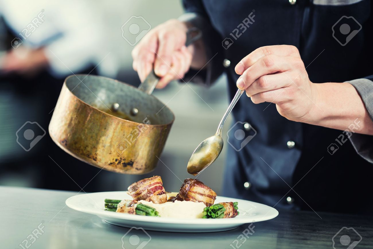 Chef pouring sauce on dish in restaurant kitchen, crop on hands, filtered image Standard-Bild - 57677056