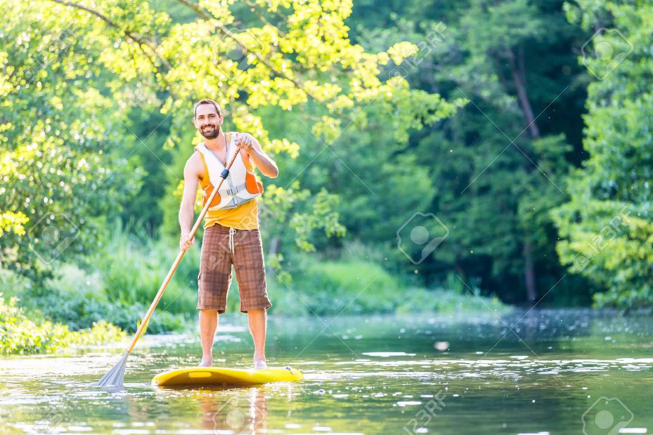 Man paddling on SUP in river Standard-Bild - 57677120