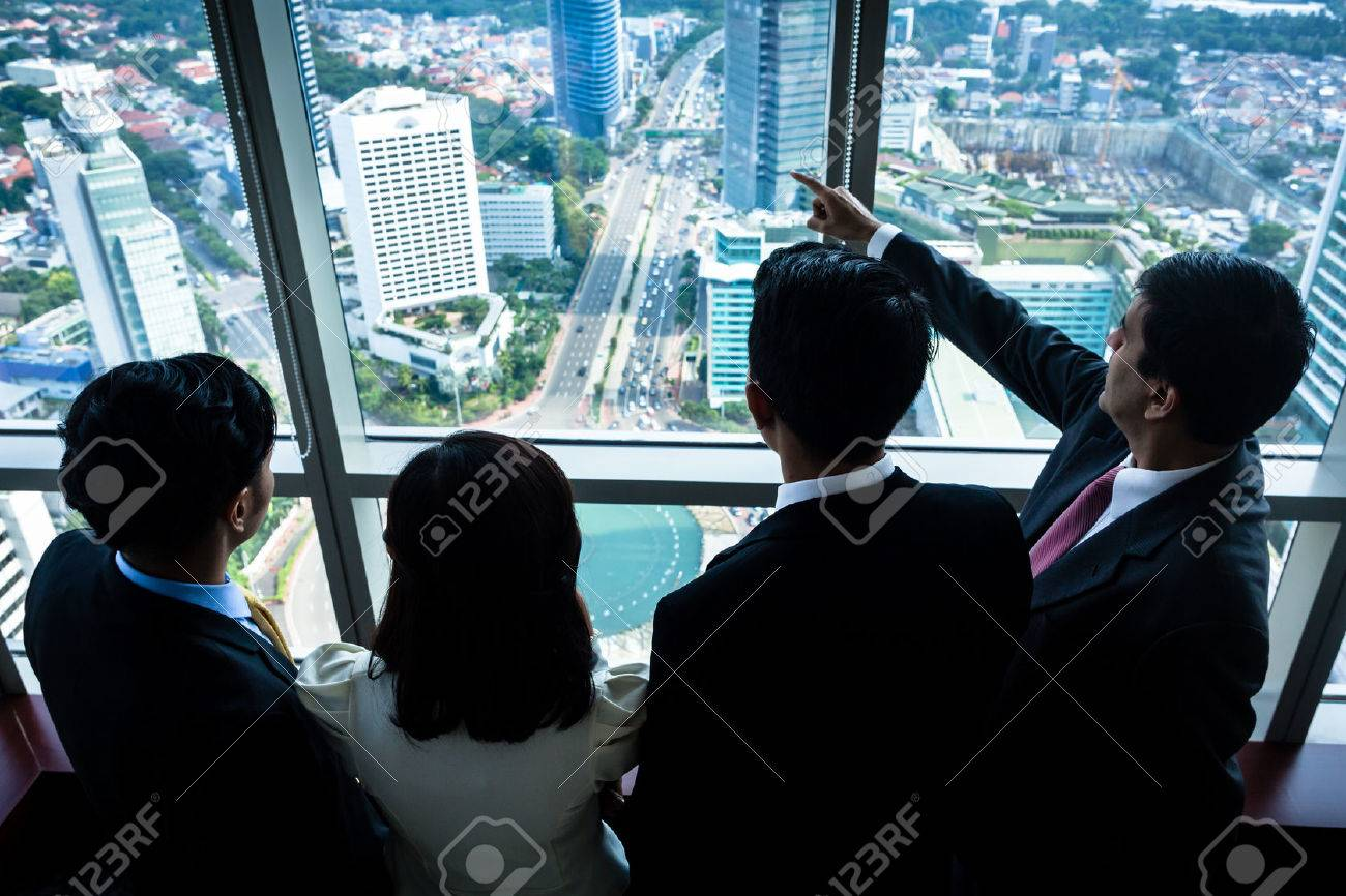 Group of Asian real estate business people looking at city skyline from skyscraper office building Standard-Bild - 63374342