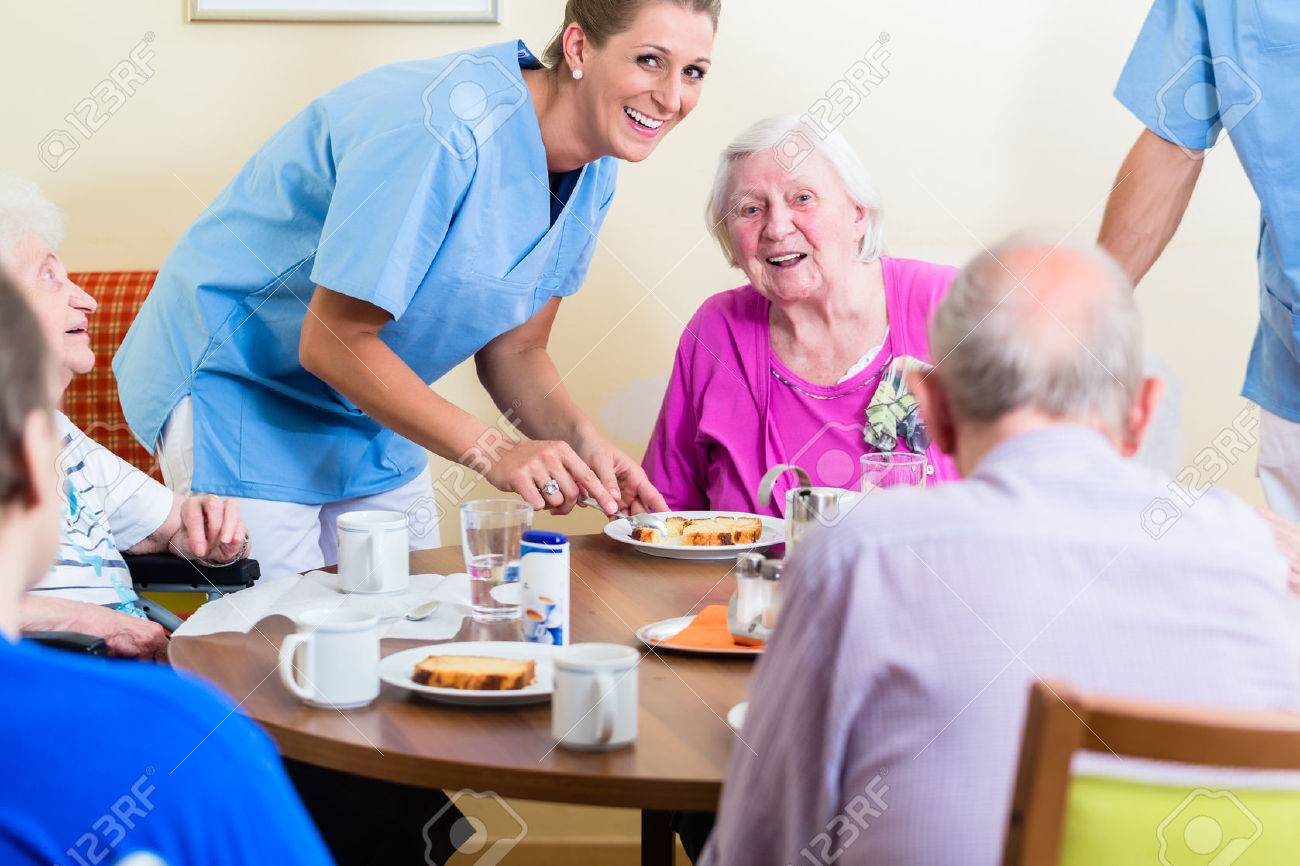 Group of seniors having food in nursing home, a nurse is serving Standard-Bild - 61779241