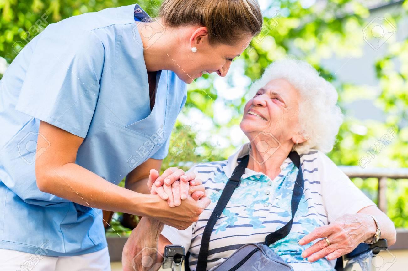 Nurse holding hand of senior woman in pension home Standard-Bild - 61779246