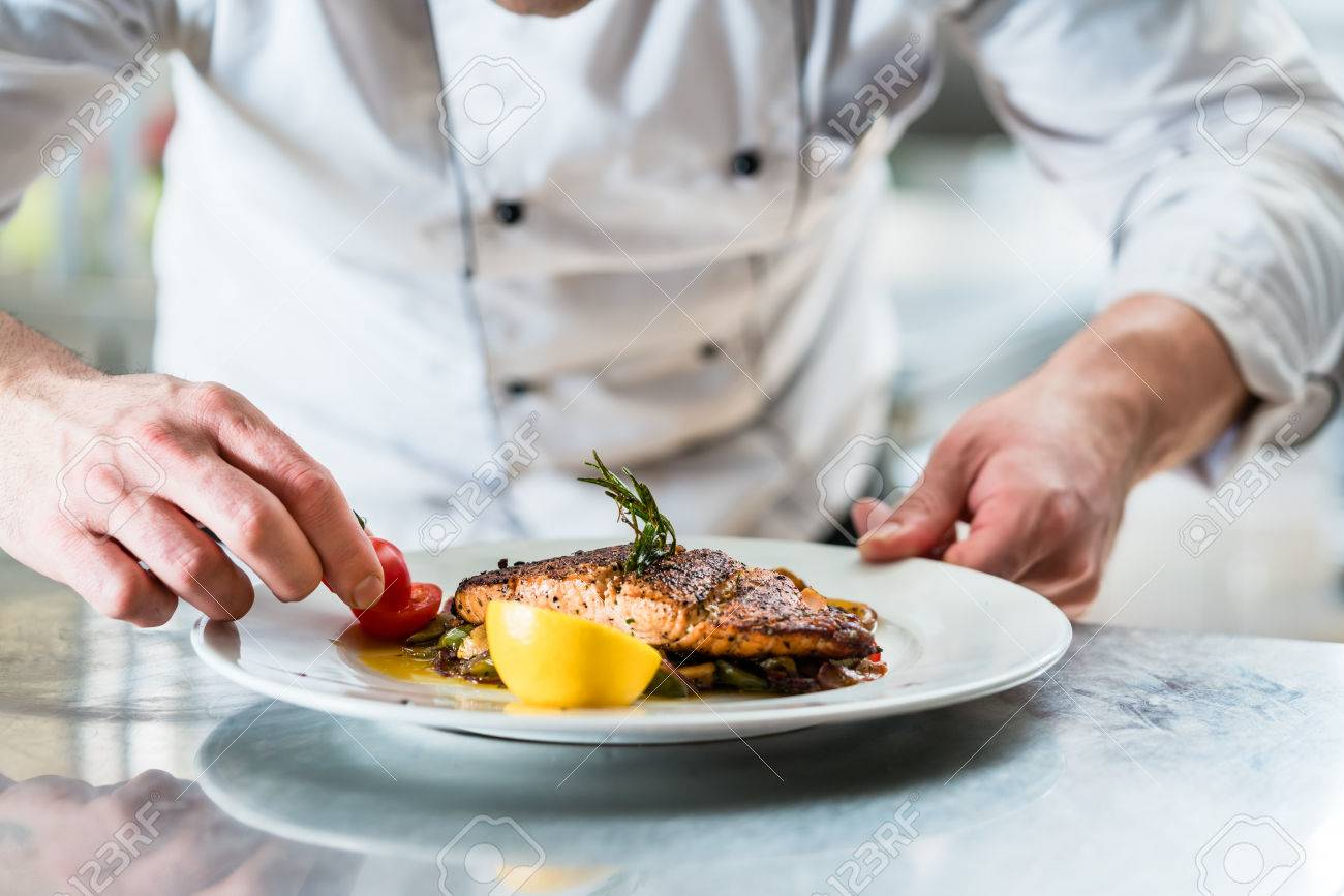 Chef with diligence finishing dish on plate, fish with vegetables - 62395276