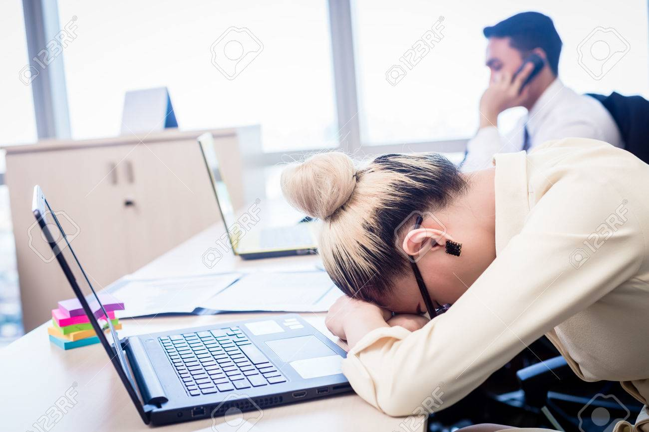 Young Asian business woman taking nap in office being exhausted and overworked Standard-Bild - 63375242