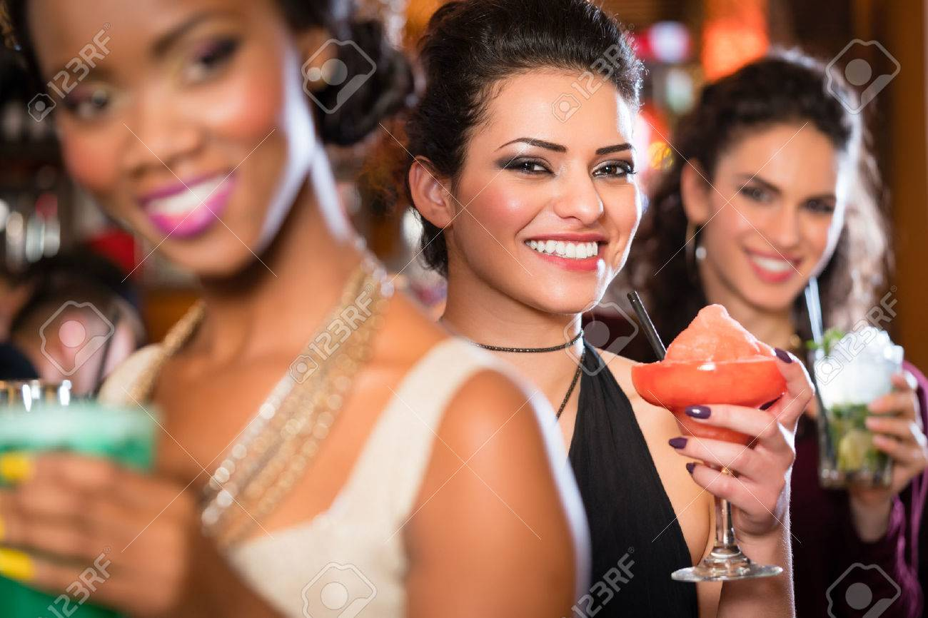 Multicultural group of women after work drinking cocktails in bar - 63375245