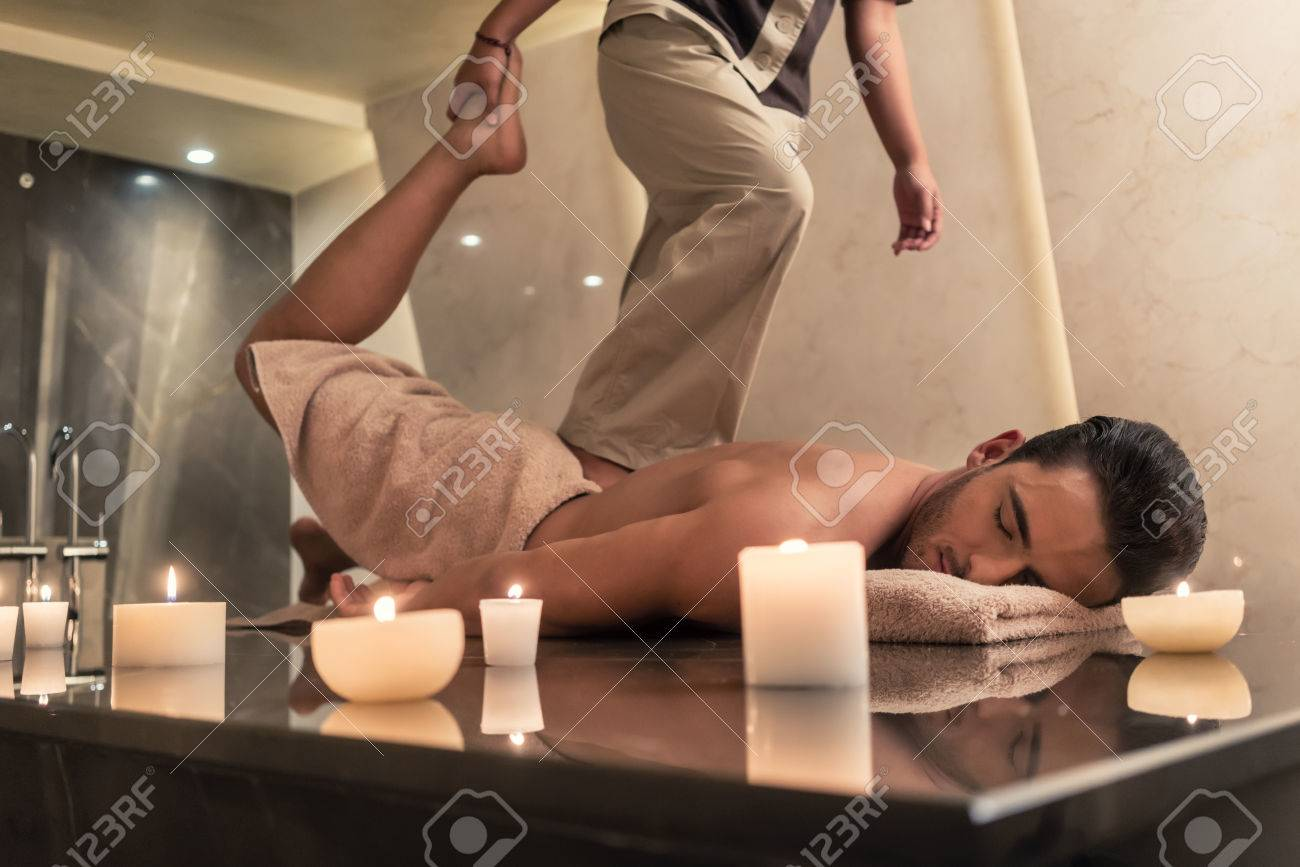 Thai massage practitioner massaging young man through traditional stretching techniques in a luxury spa and wellness center Standard-Bild - 75581227