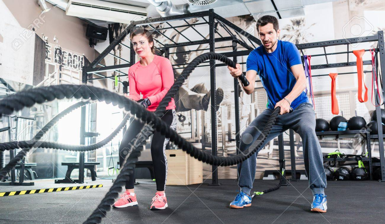 Woman and man in gym functional training with battle rope exercising - 84416549