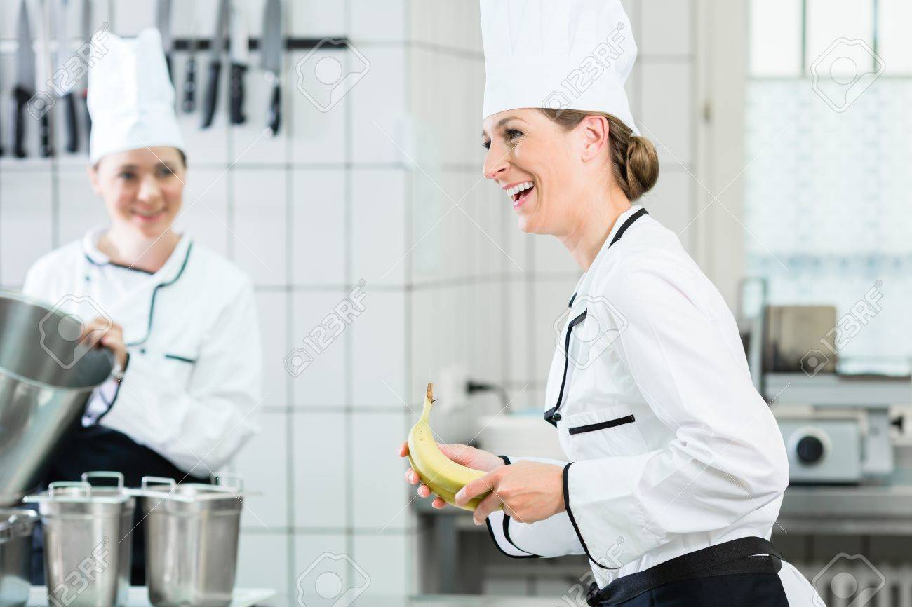 Two Female Chefs In Gastronomic Kitchen Wearing White Cooking
