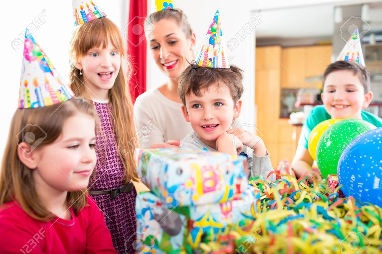 Child Unwrapping Birthday Gift With Friends At Home Party Mom Is Helping Stock Photo