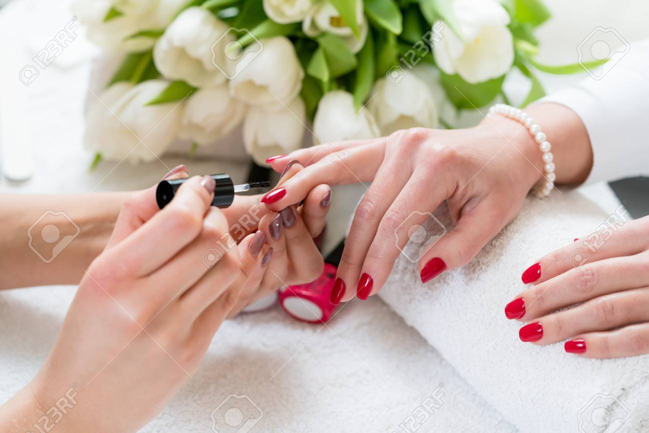 Close-up Of The Hands Of A Skilled Manicurist Applying Elegant ...