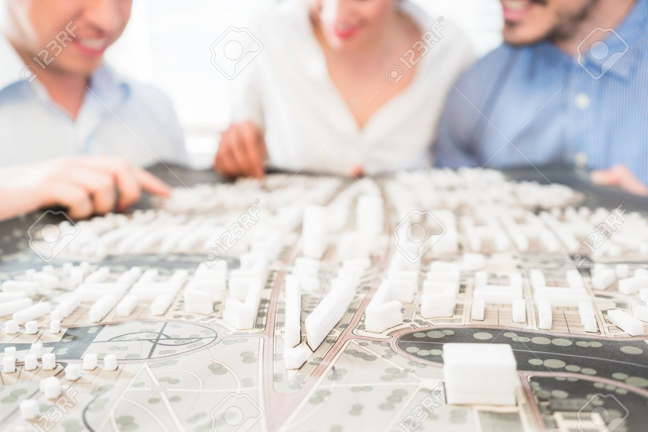 Architects or civil engineers with model for urban development in the office - 89273646