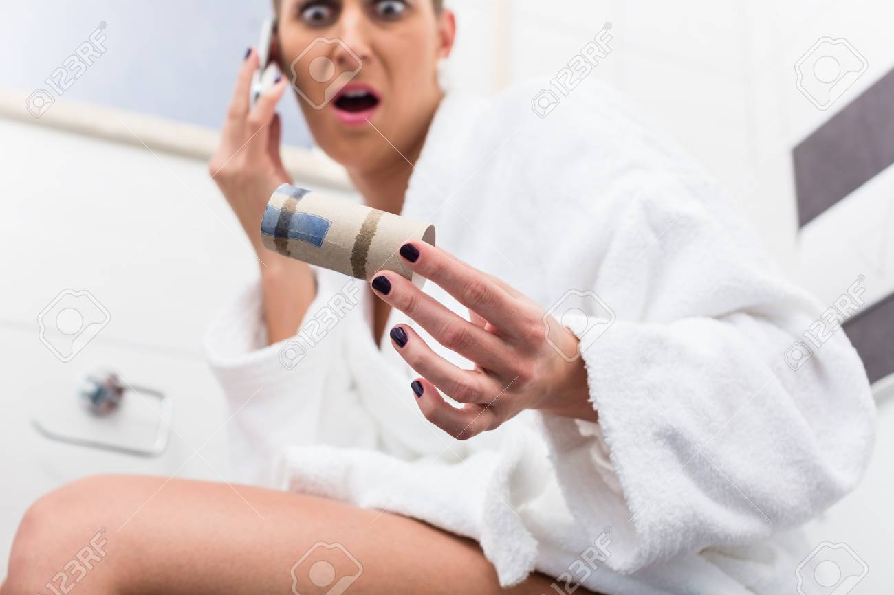Woman in bathroom sitting on toilet and complaining via phone about lack of paper - 90443513