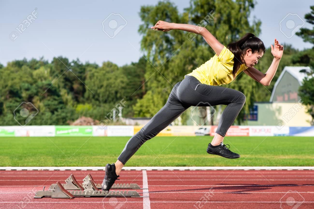 Female sprinter leaving starting blocks on running track in stadium - 91680506