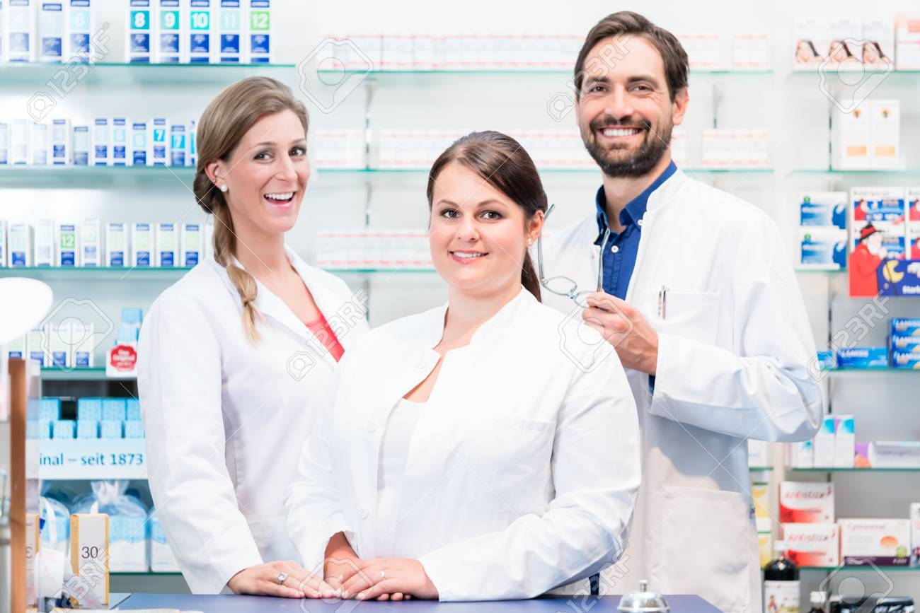 Team of apothecaries in pharmacy standing in front of shelf with prescription drugs - 91453380