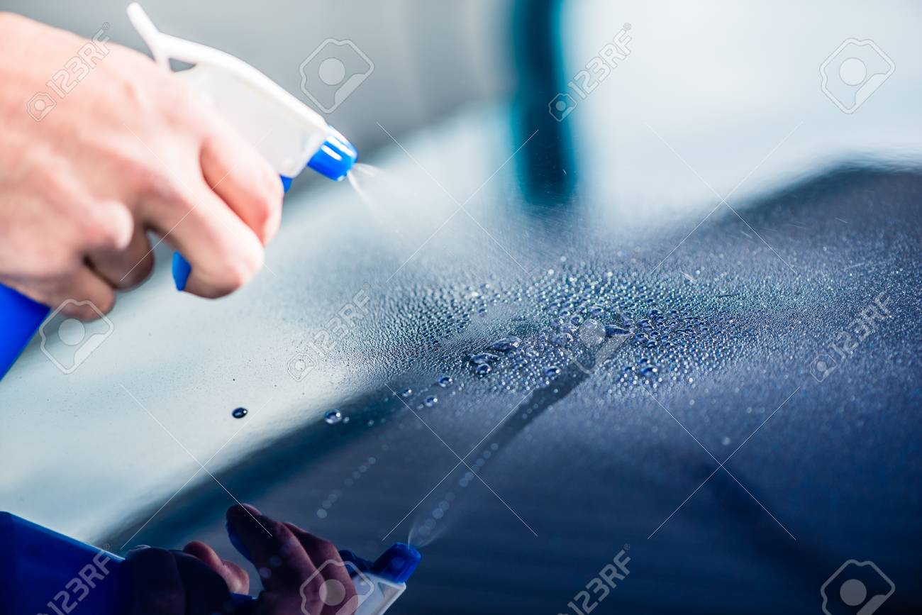 Close-up of hand spraying cleaning substance on the surface of a blue car at auto wash - 92863074