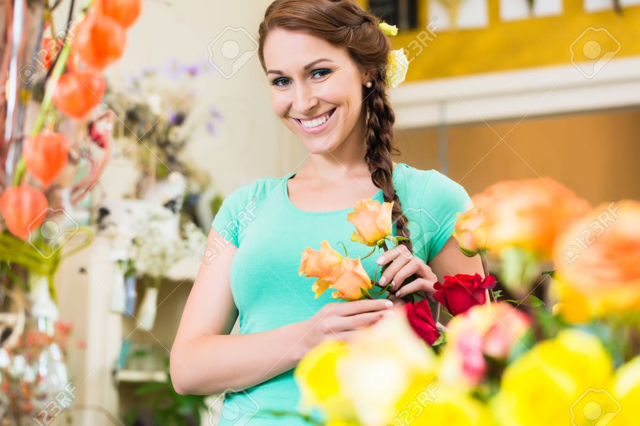 Florist Or Customer With Flowers In Shop Looking At Camera