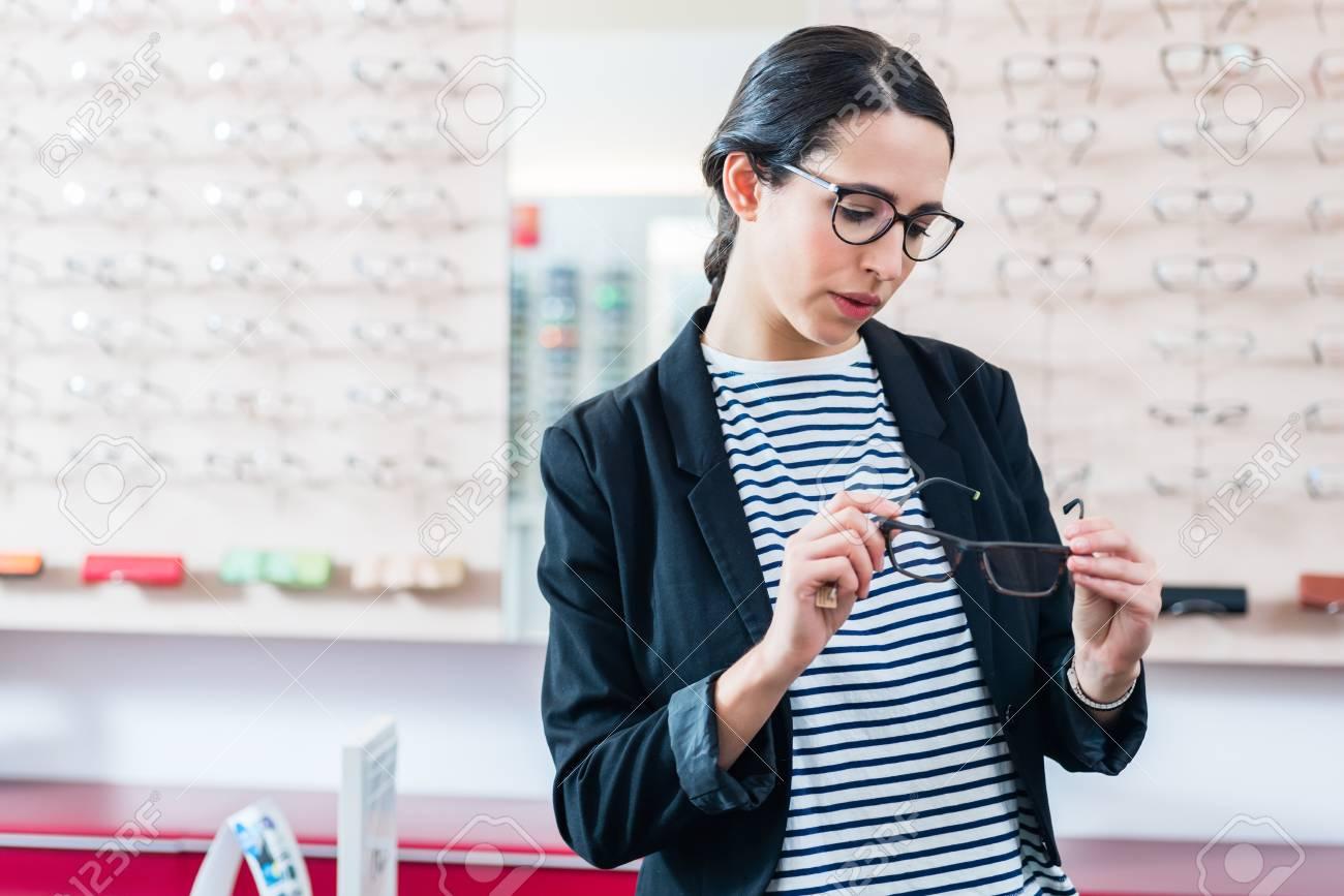 a8a5dd793c Woman choosing glasses in optician shop Stock Photo - 95431990