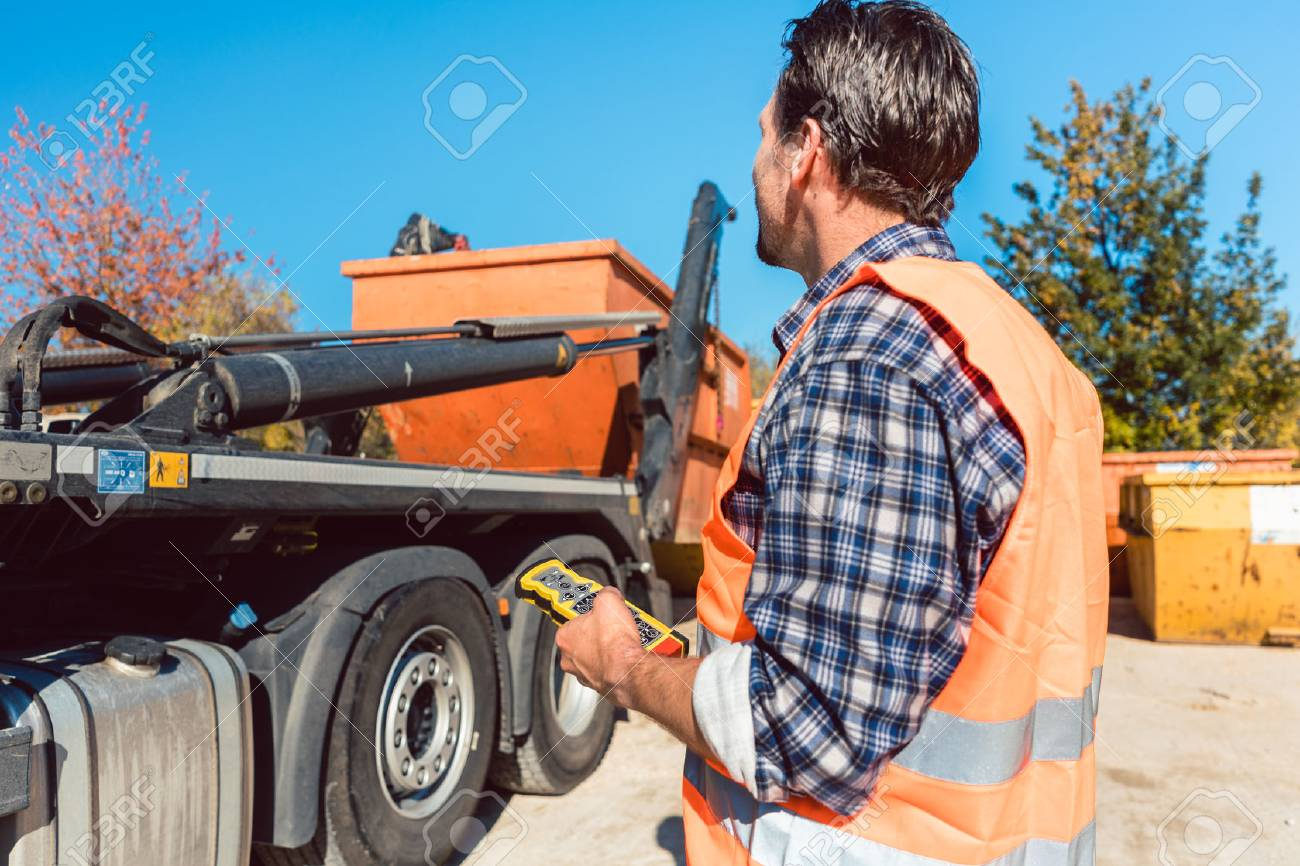 Worker on construction site unloading container for waste from truck using remote control - 96032017