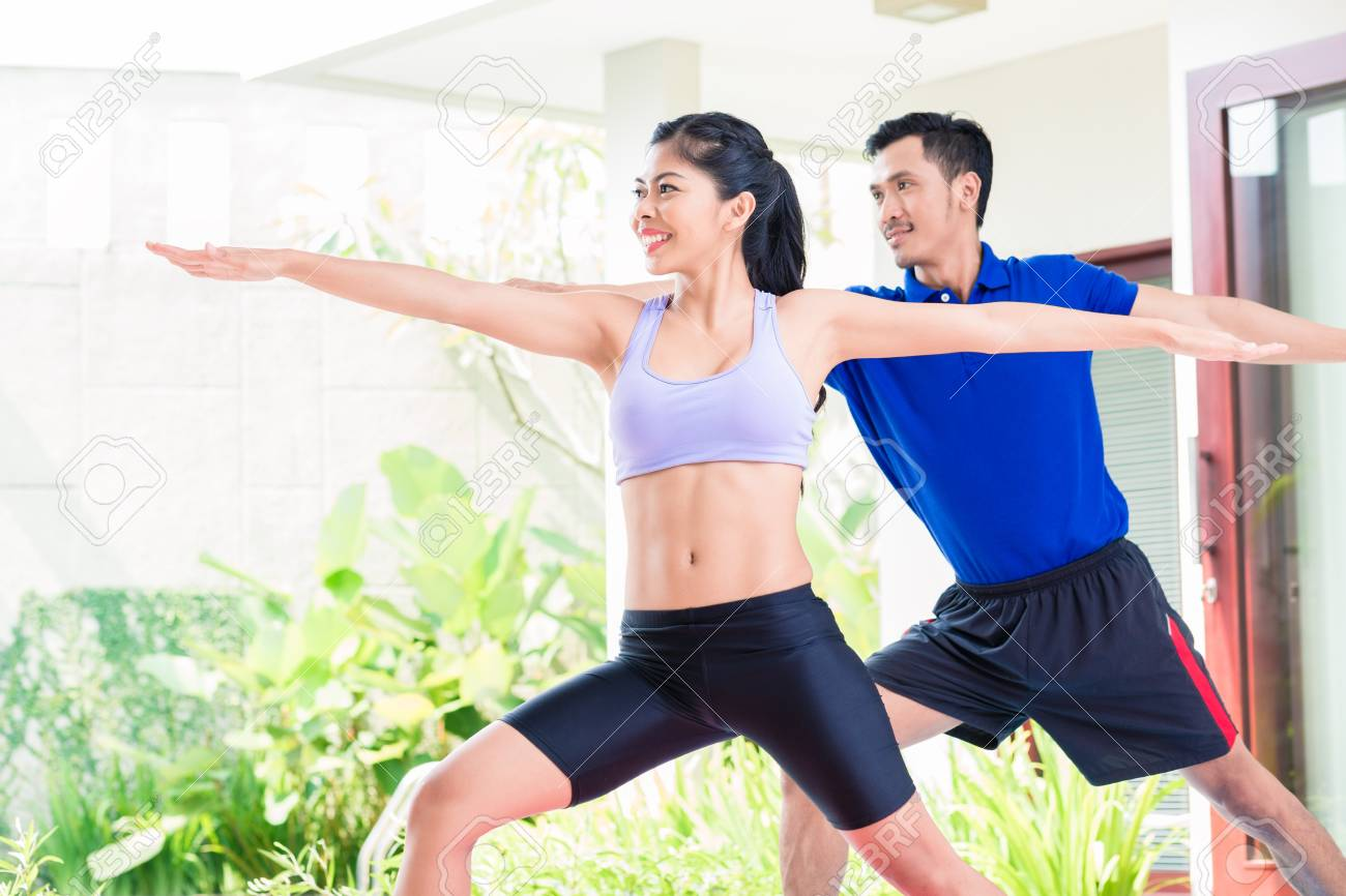Happy Asian fitness couple at sport workout in tropical home - 105701214