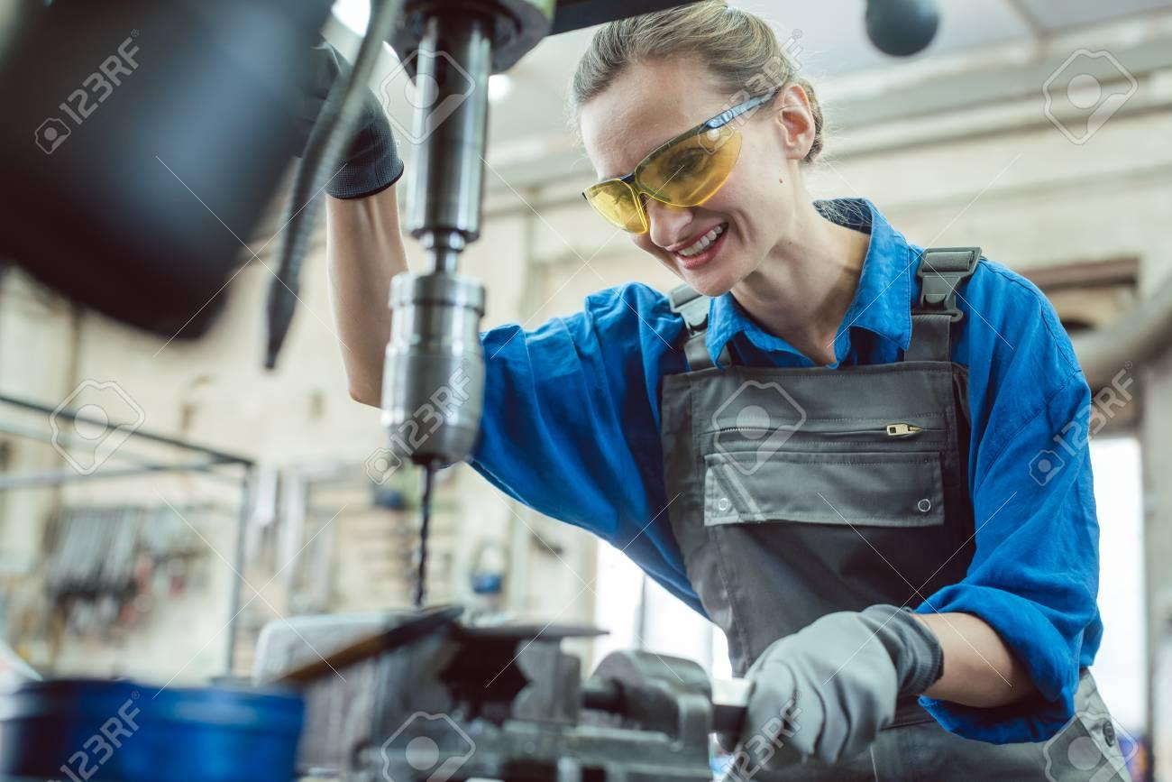 Woman worker in metal workshop using pedestal drill to work on piece - 110440249