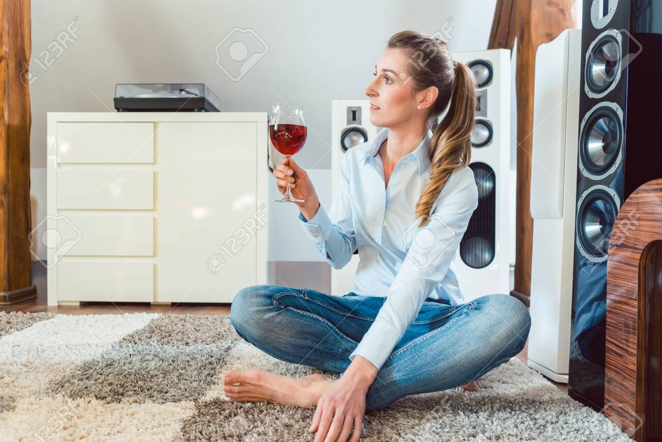 Woman having glass of wine in front of Hi-Fi speakers enjoying the drink and the music - 120443164