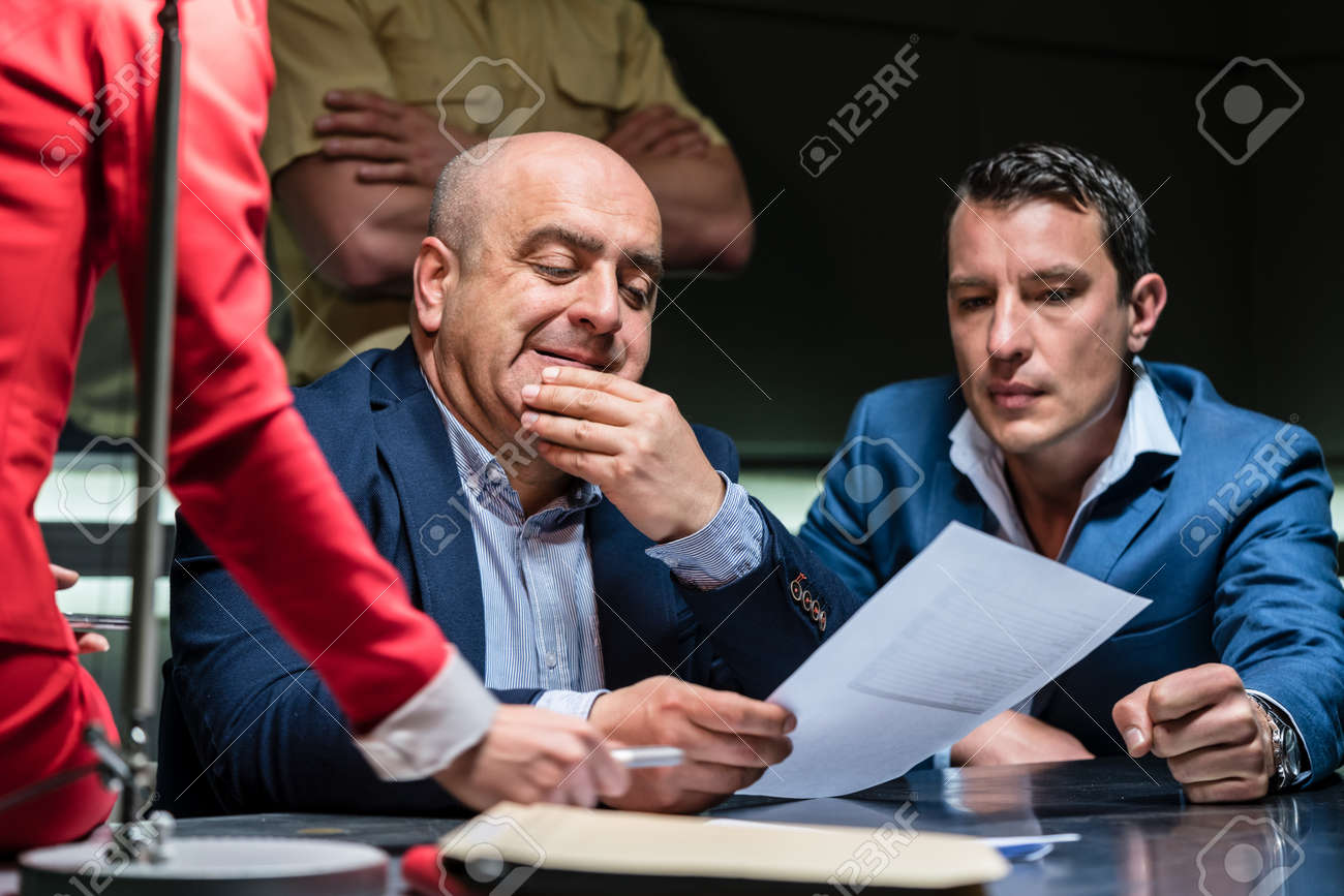Portrait of a middle-aged man calling his attorney in order to ask for legal assistance, under the pressure of a difficult interrogation at the police - 122674225