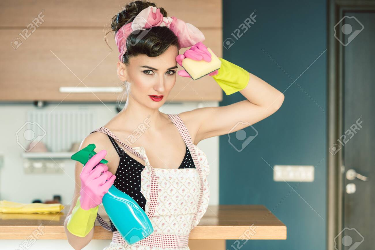 Housewife woman in retro outfit attempting to clean the kitchen wiping sweat from forehead - 123737451