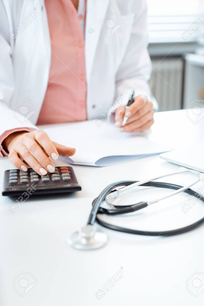 Closeup of doctor using calculator writing bills and doing bookkeeping - 126648920