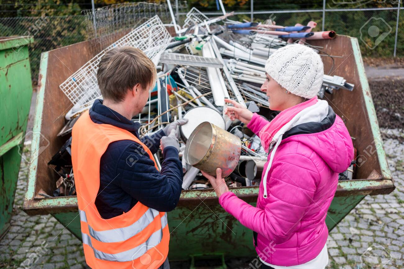 Woman putting lots of scrap metal in container to be recycled - 131709001