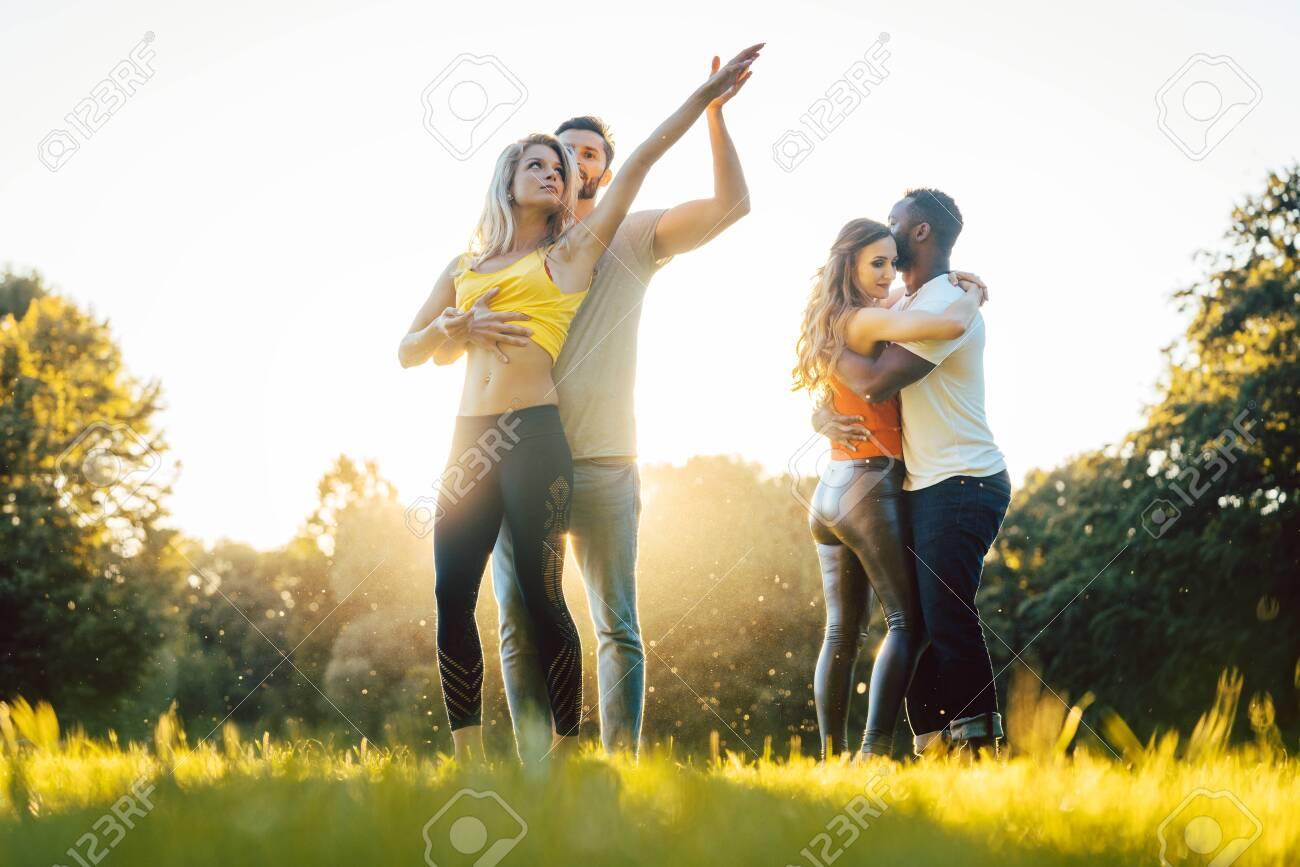 Group of people dancing Kizomba in golden sunset - 135521608