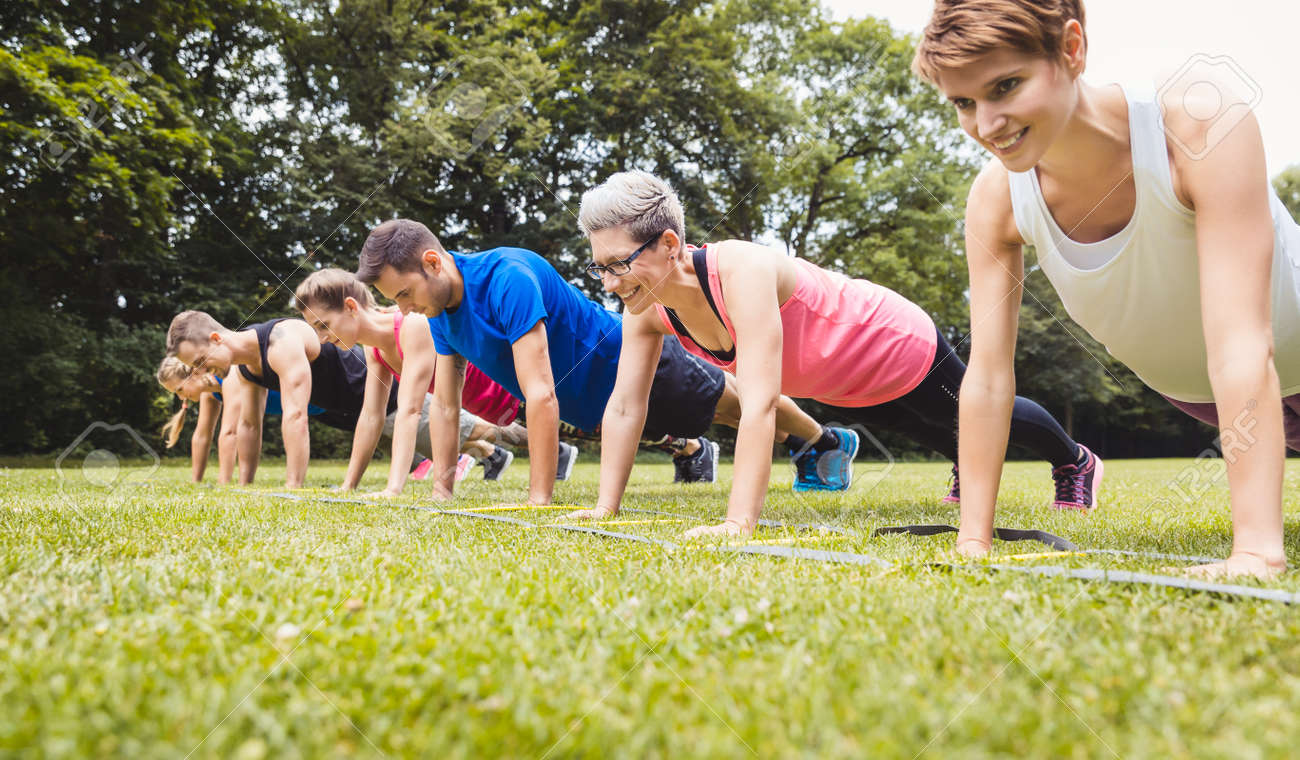 Fitness group practising push-ups in park - 168625252