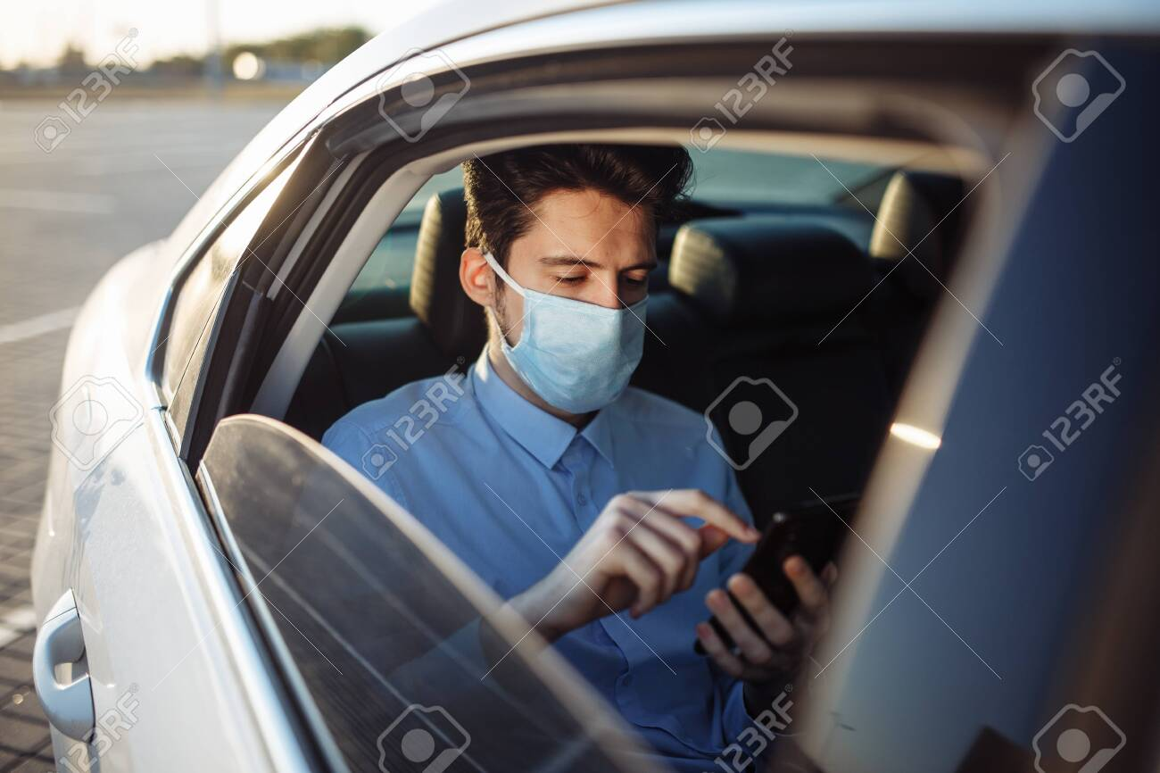 Young businessman takes a taxi and looks into his cell phone wearing sterile medical mask. A man sits on the back seat of taxi and takes a ride during coronavirus pandemic. Social distance concept - 151473528