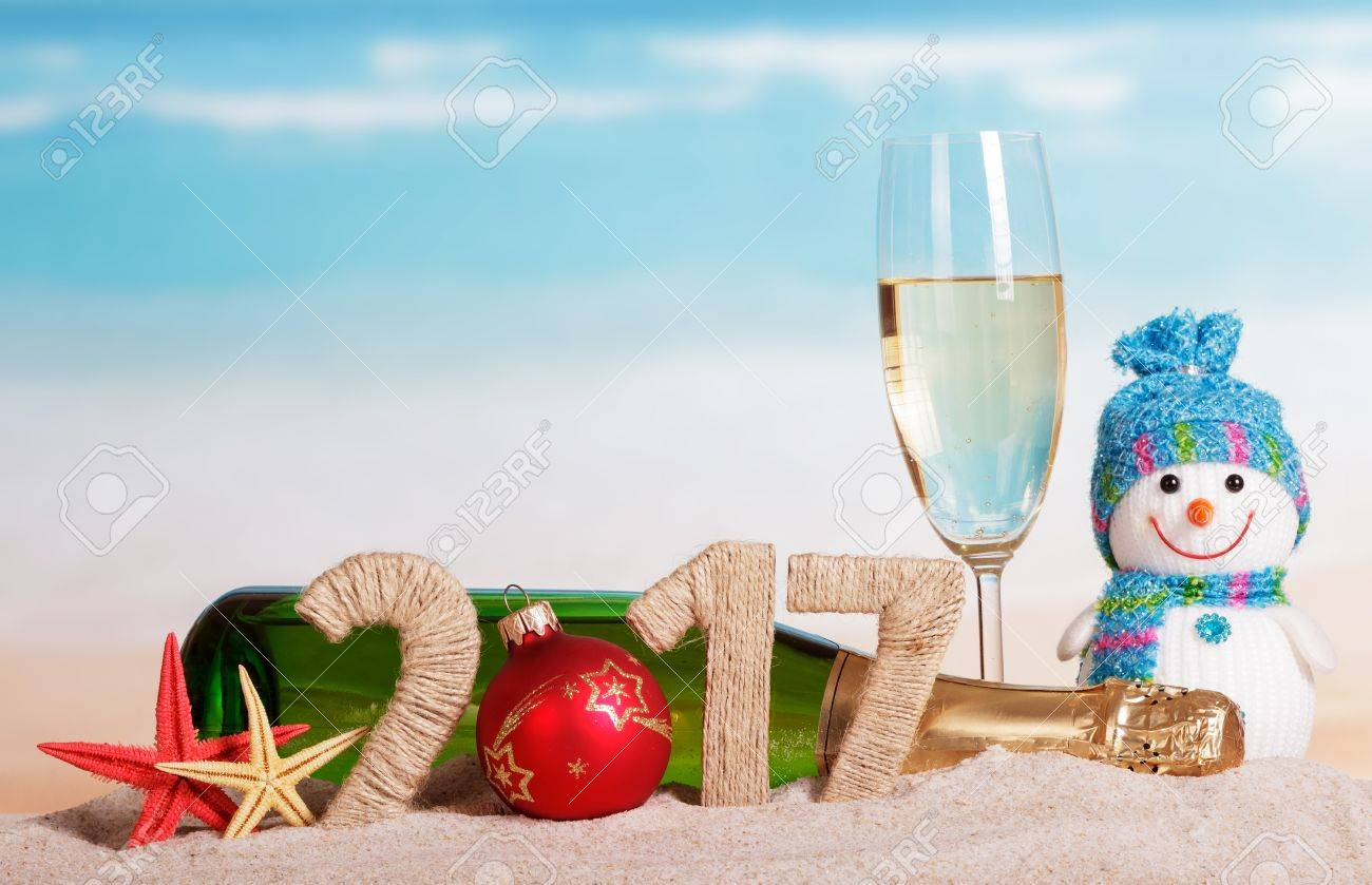Christmas ball instead of the number in the amount of 2017 champagne bottle and glass, snowman and starfish in the sand against the sea. - 65499436