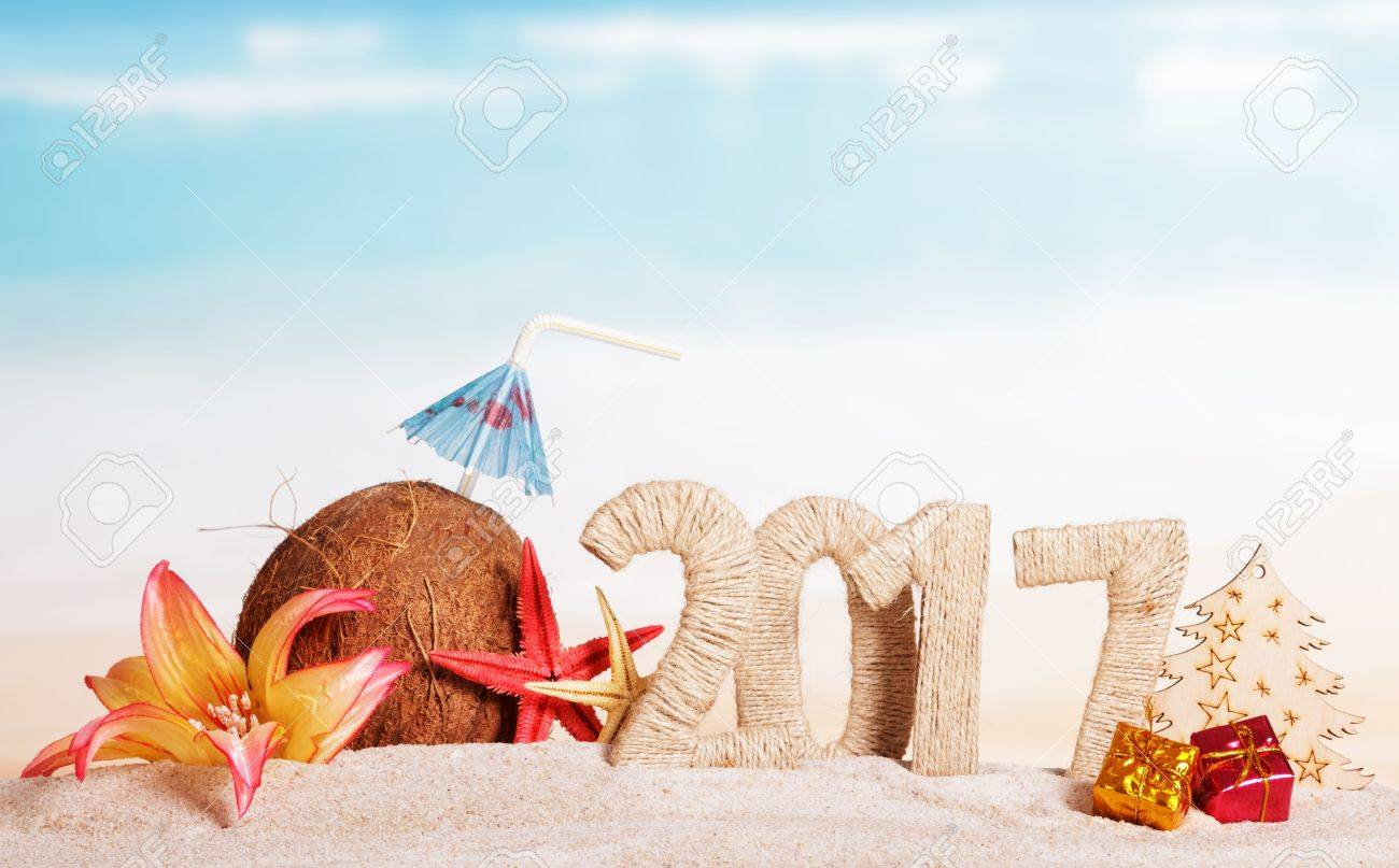 Coconut, number 2017, starfish, flower, tree and Christmas presents in the sand against the sea. - 65487914