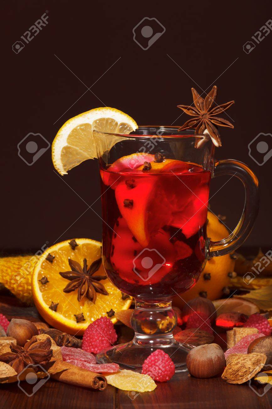 Mulled wine with orange, cloves, anise and cinnamon on a brown background. - 65503338