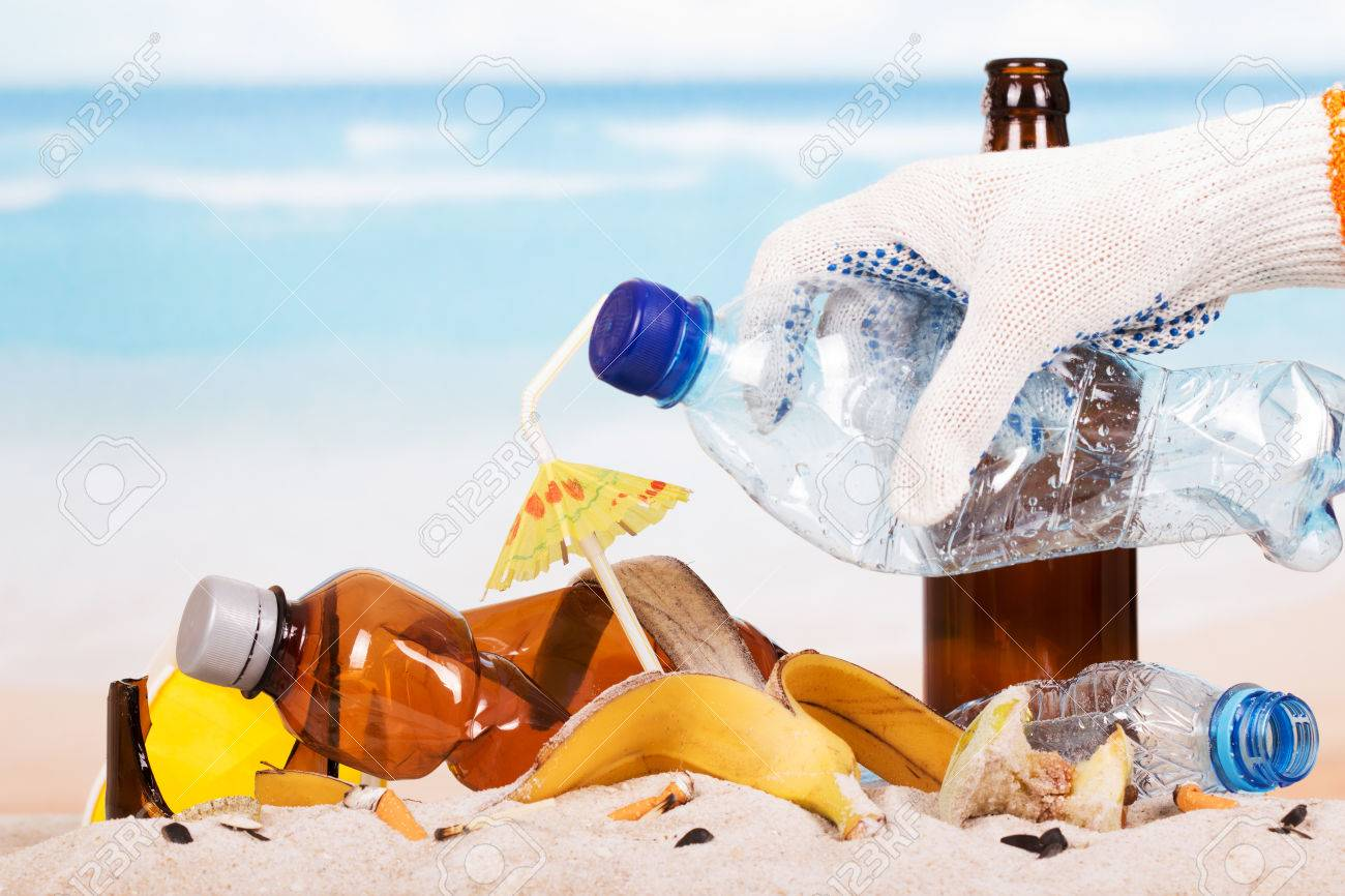 Hand holding a plastic bottle on a pile of garbage in the sand background. - 67390794