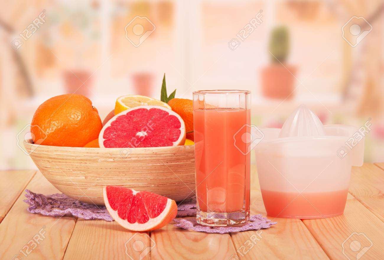 A Bowl Of Whole And Parts Of Citrus A Glass Of Grapefruit Juice
